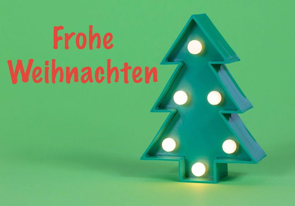 Frohe Weihnachten in roter Schrift auf grünem Hintergrund mit beleuchtetem Weihnachtsbaum
