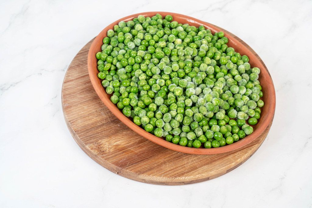 Frozen Green Peas in the bowl above white background