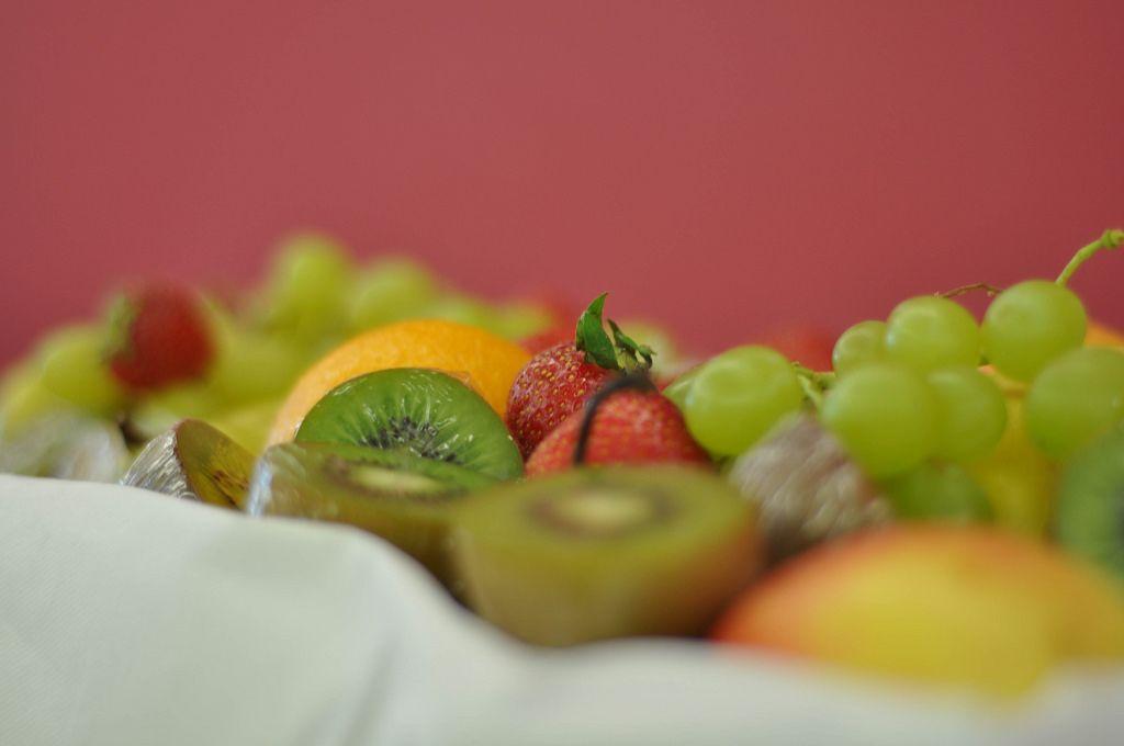 Früchtekorb mit Kiwi, Erdbeeren, Trauben, Orangen und Äpfeln