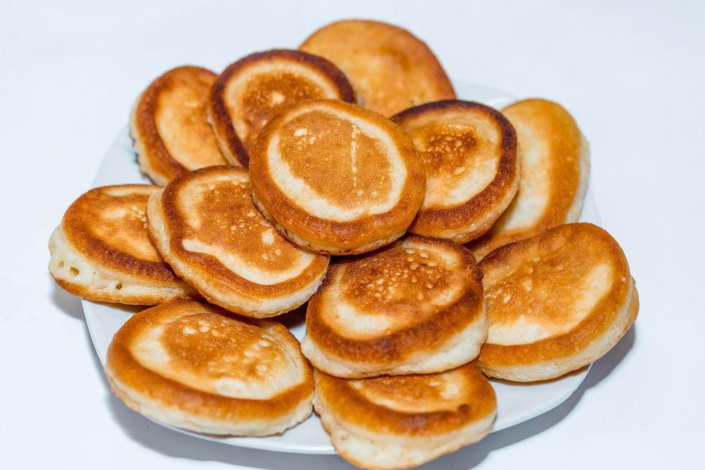 Frühstück aus selbstgemachten, dunkel gebratenen Pfannkuchen auf Teller gestapelt