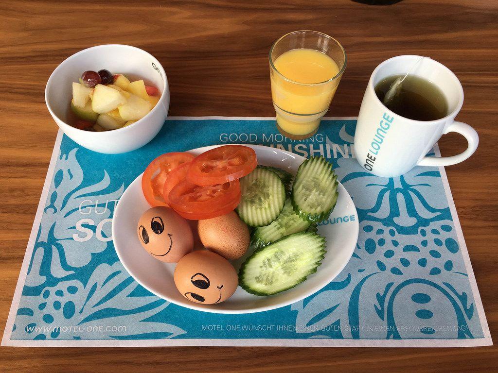 Frühstück mit Obstsalat, O-Saft, Gurken, Tomaten und Eiern