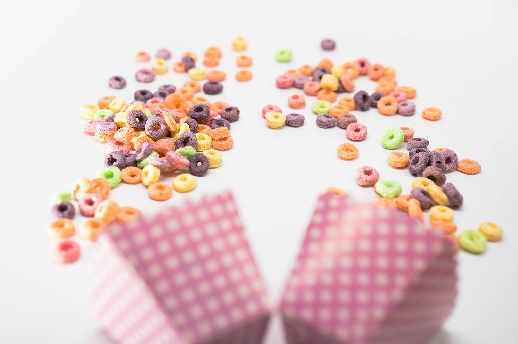 Fruit Loops fallen aus pinken Snackschachteln auf weißem Untergrund