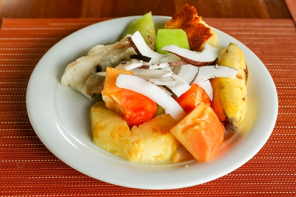 Fruit salad with pineapple, coconut, banana and papaya on white plate