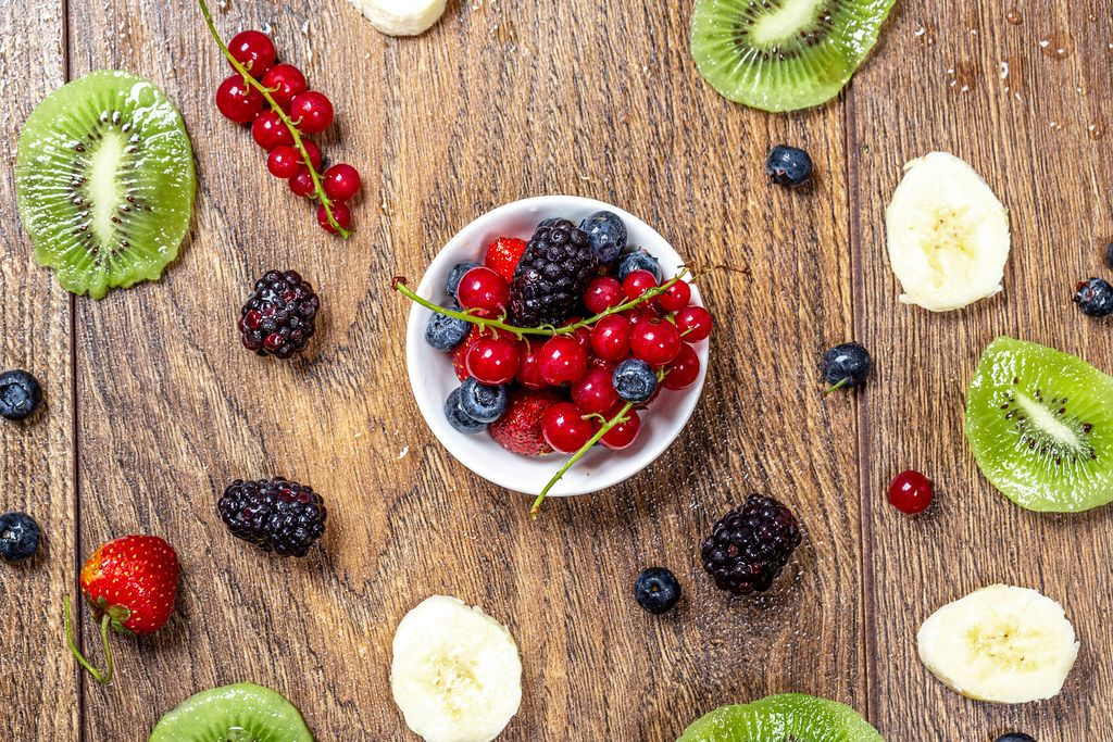 Fruit summer background with berries, kiwi slices and banana