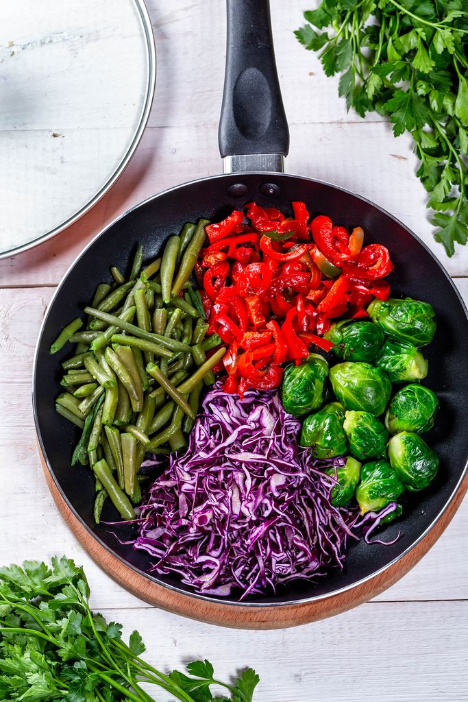 Frying pan with Brussels sprouts, pepper, asparagus and red cabbage. Top view