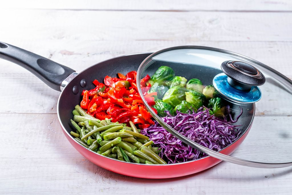 Frying pan with sliced vegetables on white wooden table