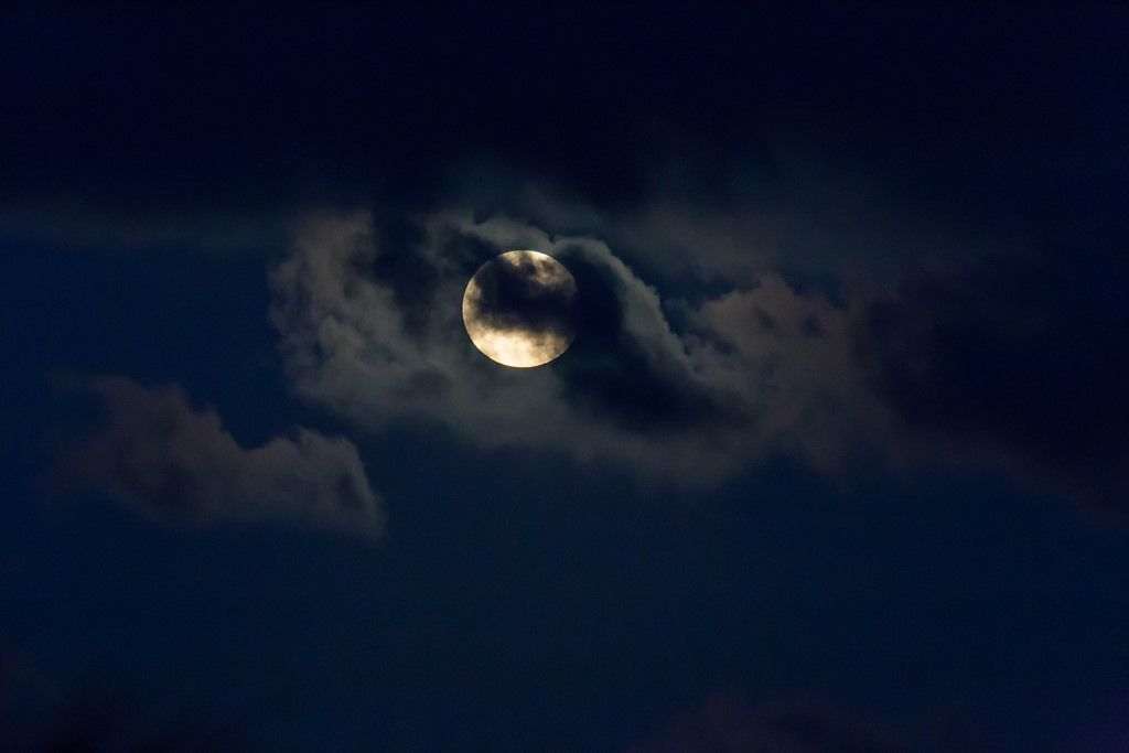 Full moon partially covered by clouds