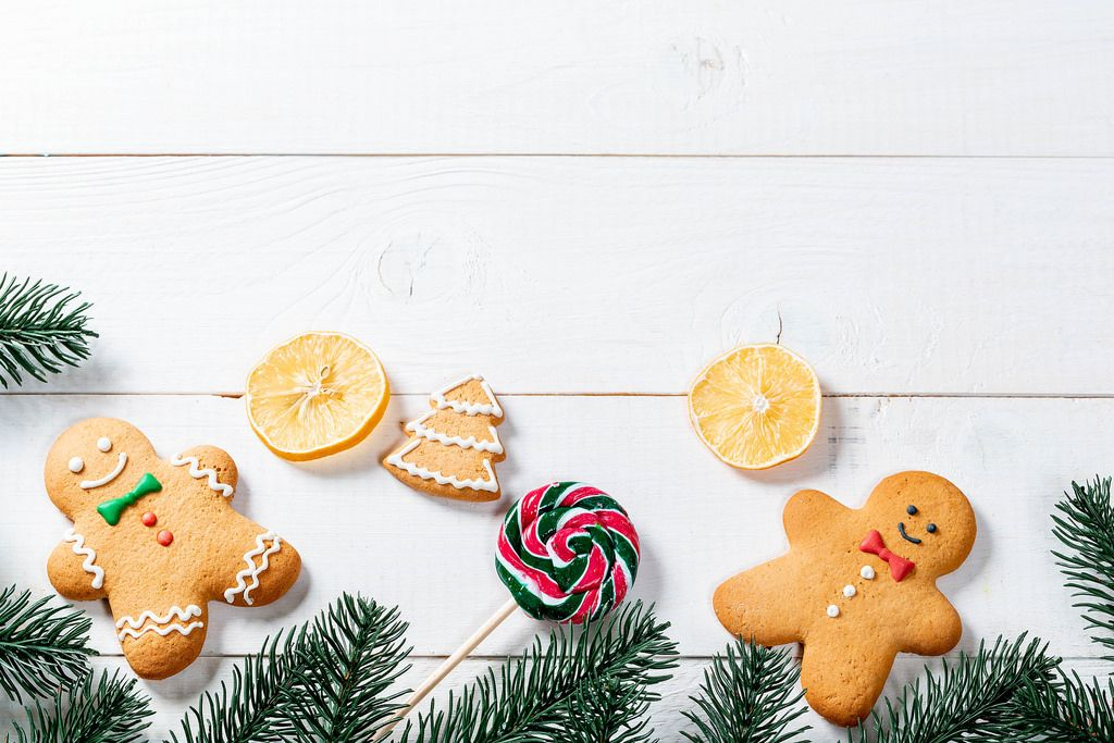Funny gingerbread men with tree branches and candy