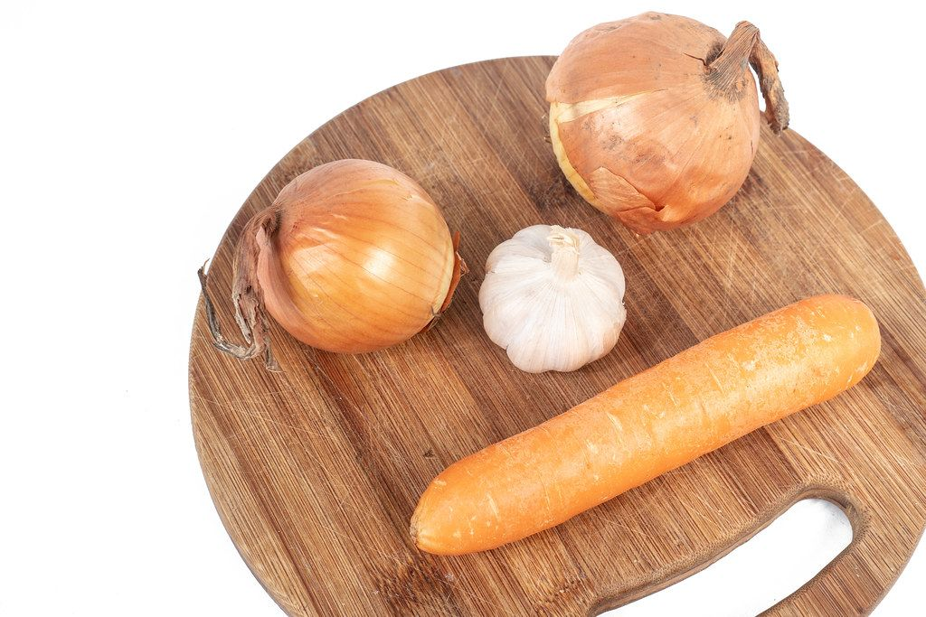 Funny image with Onion Garlic and Carrot on the wooden board