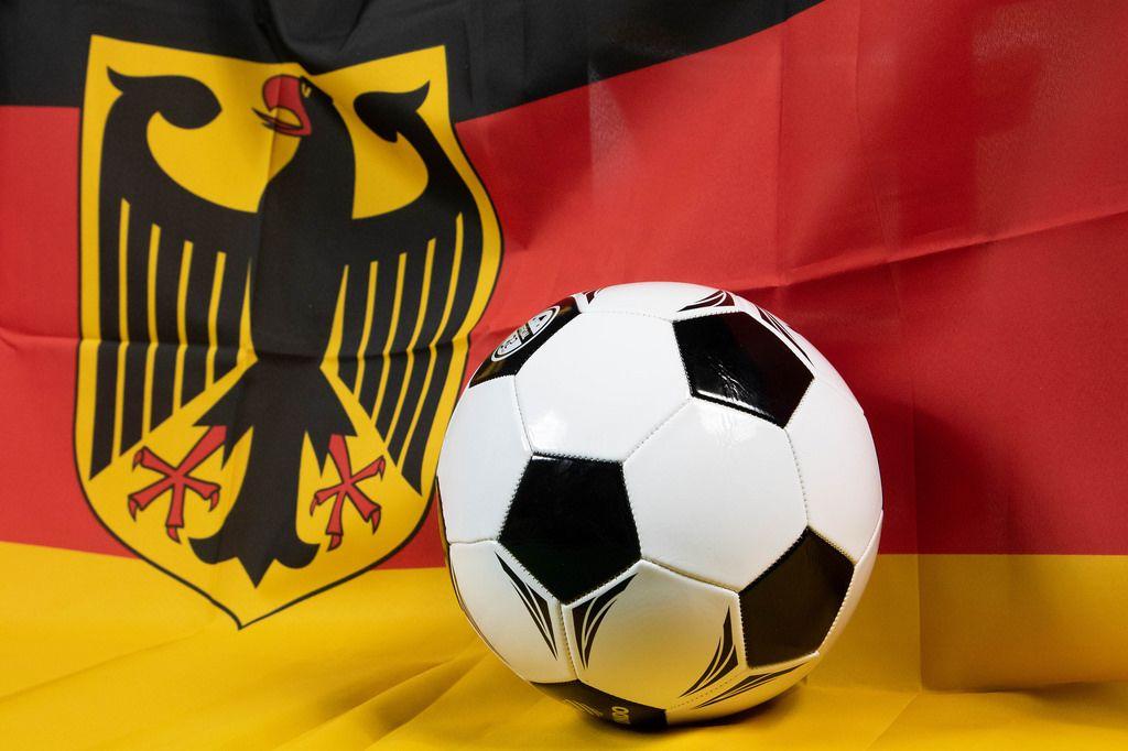 Fußball mit Flagge Deutschlands im Hintergrund