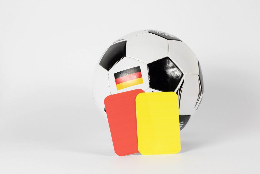 Fußball mit gelber und roter Schiedsrichterkarte vor weißem Hintergrund