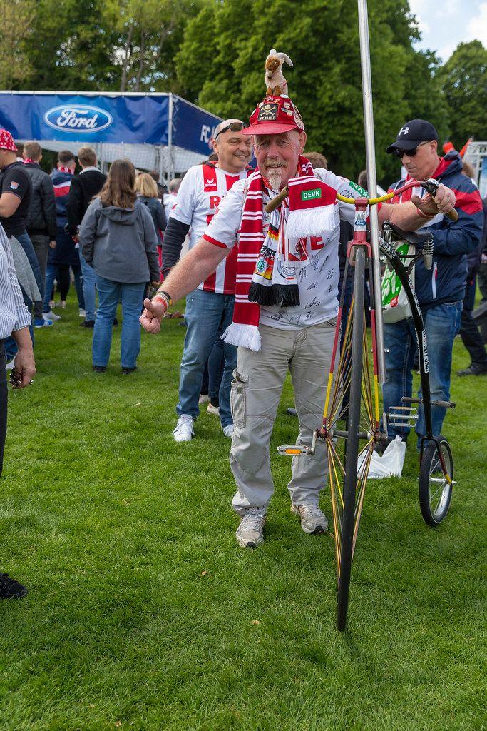 Fußballfan mit 1. FC Köln Maskottchen auf verrücktem Hut, schiebt ein Hochrad in Farben der Deutschlandflagge im RheinEnergie- Stadion Park