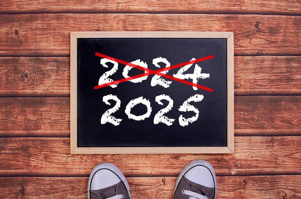 Füße vor einer Jahreszahltafel symbolisieren den Übergang und Eintritt in das Jahr 2025