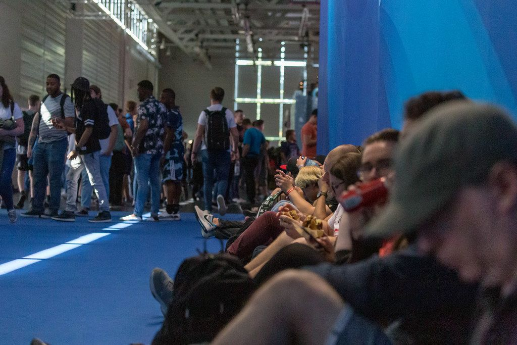 Games fair visitors taking a break from Gamescom while sitting on the floor and having lunch