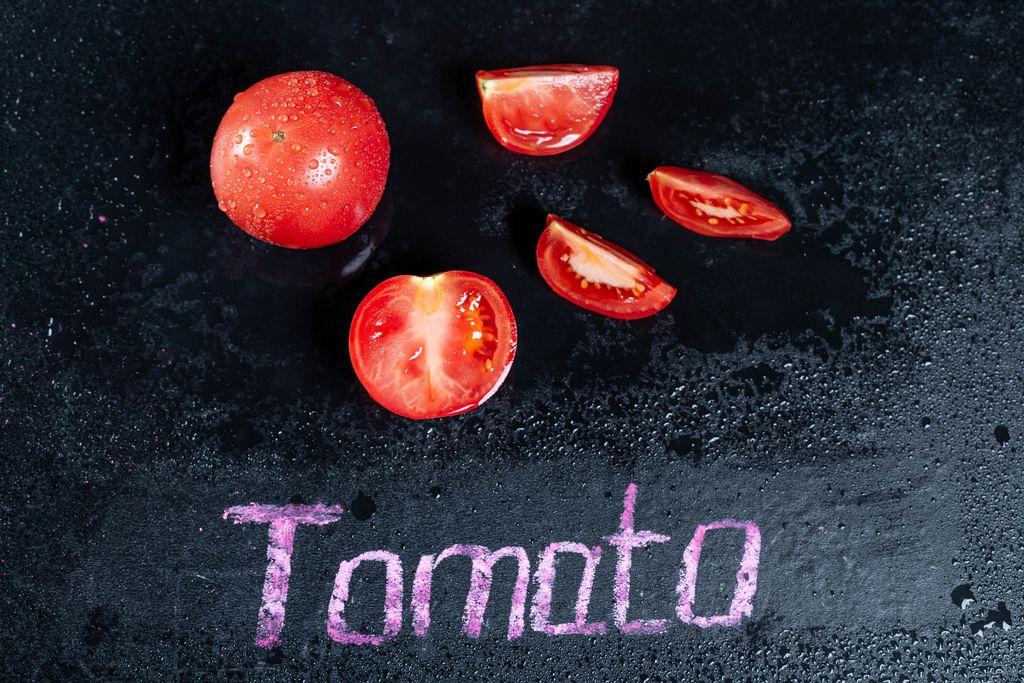 Ganze Tomaten und Tomatenstücke auf schwarzem feuchtem Hintergrund mit der Schrift Tomato