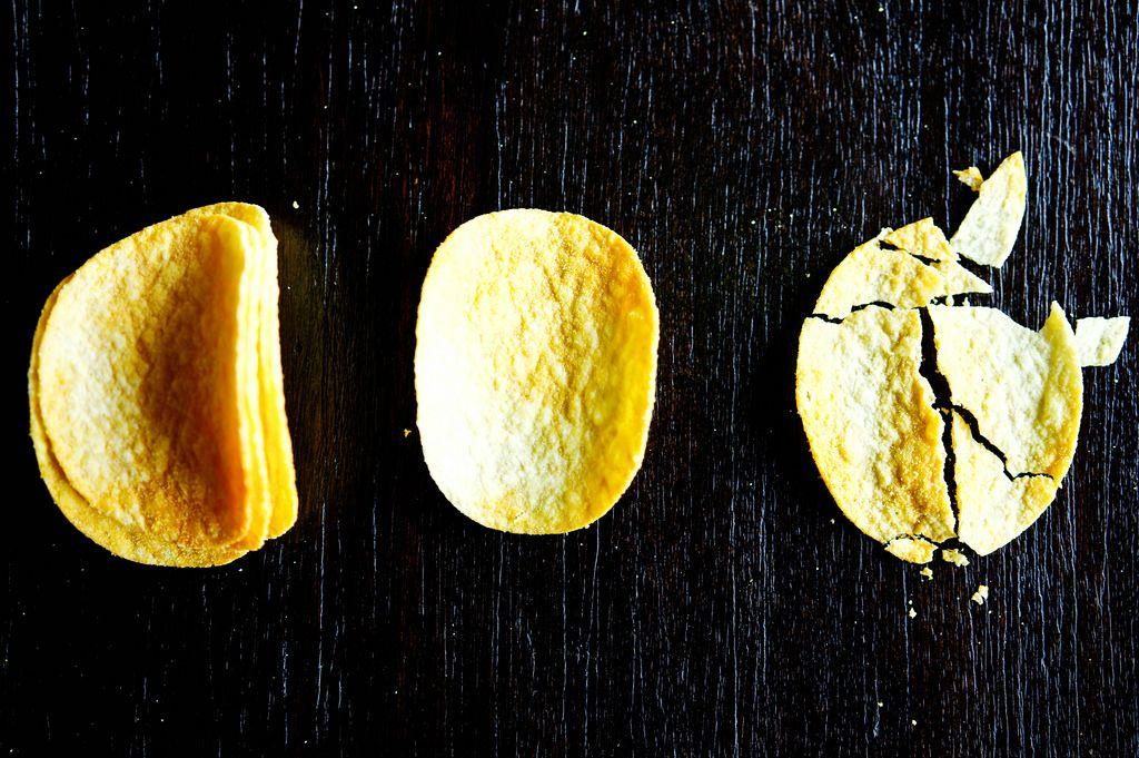 Ganze und zerbrochene Kartoffel-Chips auf schwarzem Hintergrund