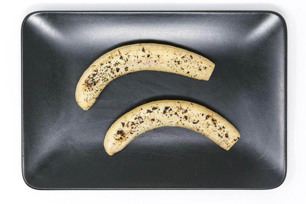 Gebackene Bananen mit geschmolzenen Schokoraspeln auf schwarzem Teller