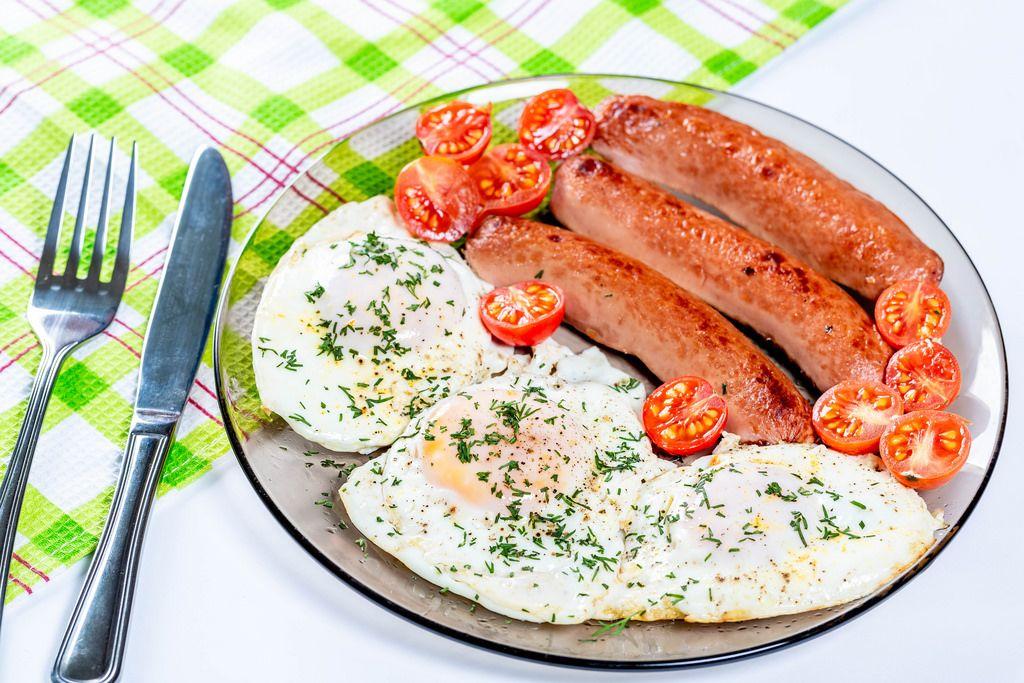 Gebratene Eier und Würstchen auf einem Teller mir Kirschtomaten auf einem Teller
