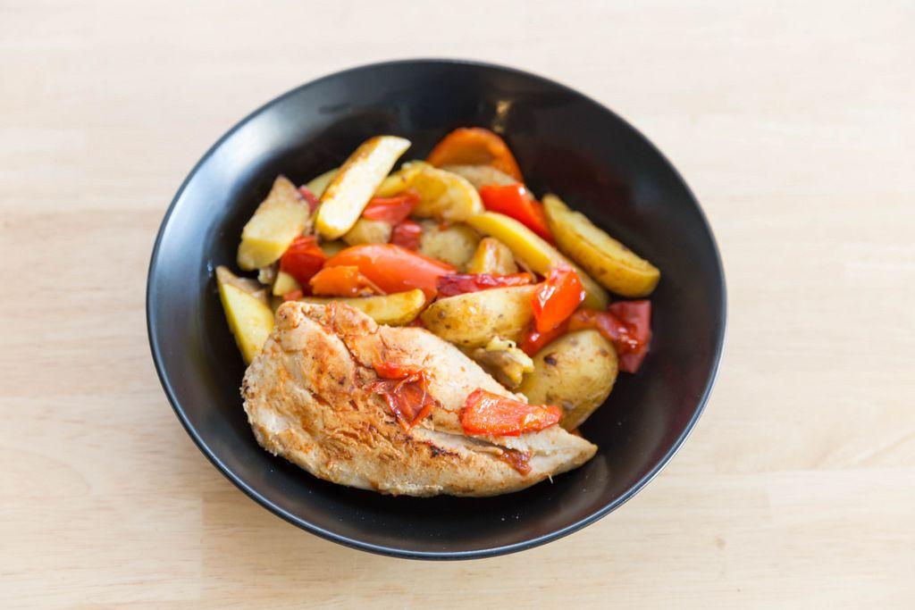 Gebratene Hähnchenbrust mit Ofenkartoffeln und Paprika auf einem schwarzen Teller