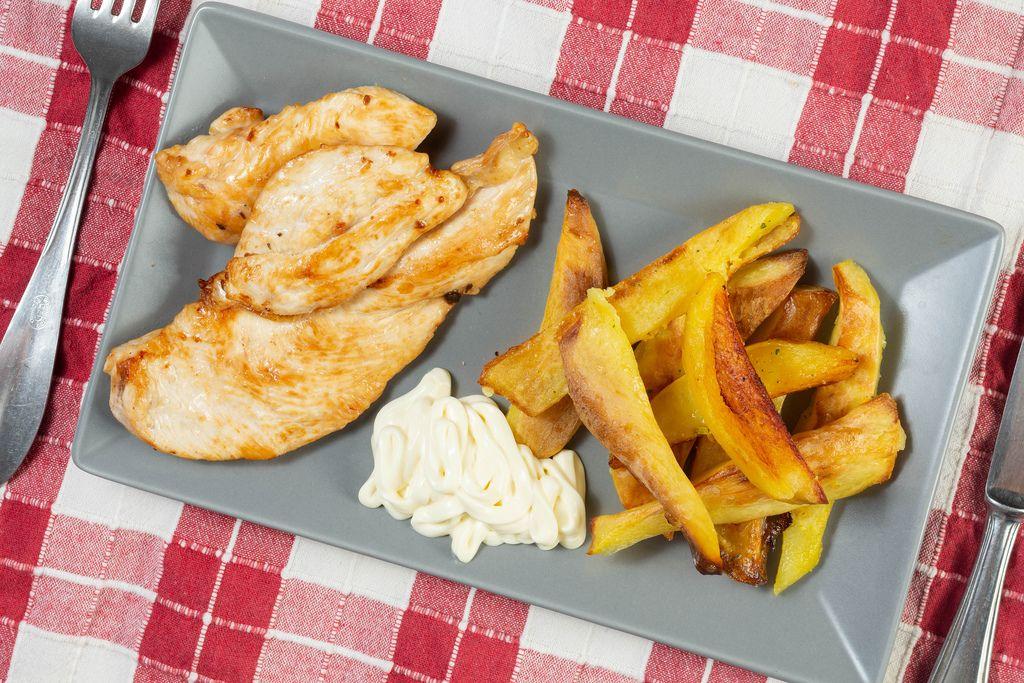 Gebratene Hähnchenfilets zu selbstgemachten Kartoffelschnitzen und Mayonnaise auf grauem Teller