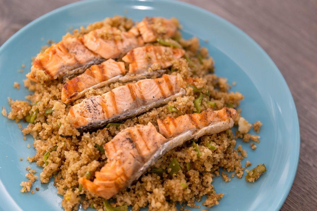 Gebratene Lachsstreifen auf Couscous, angerichtet auf blauem Teller