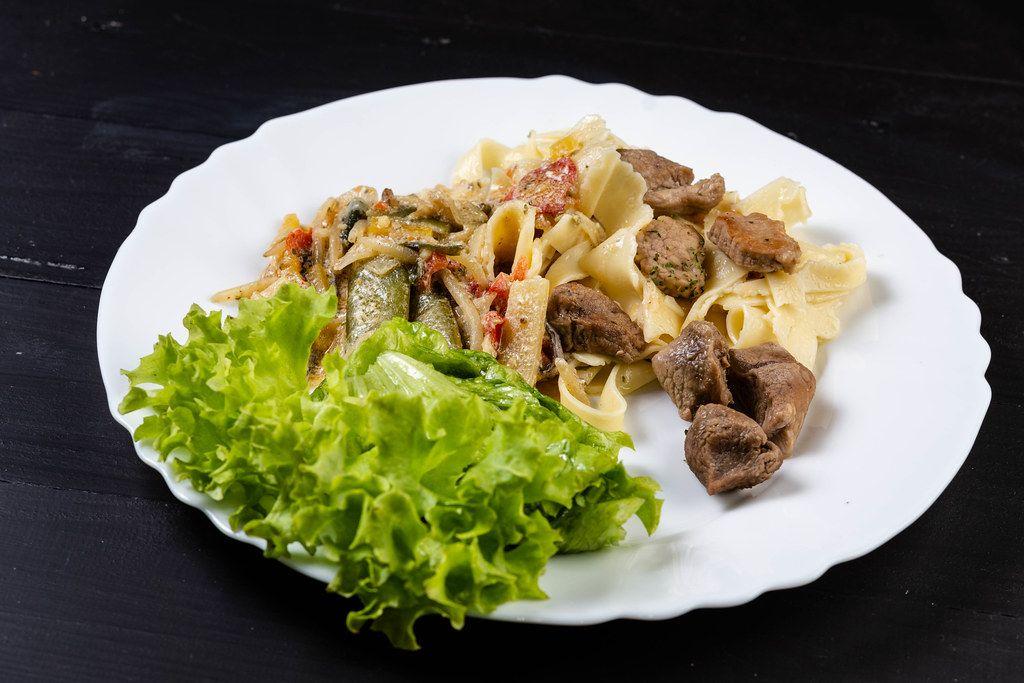Gebratenes Gemüse mit Nudeln und Schweinefleisch, mit Salat auf einem Teller angerichtet auf schwarzem Holztisch