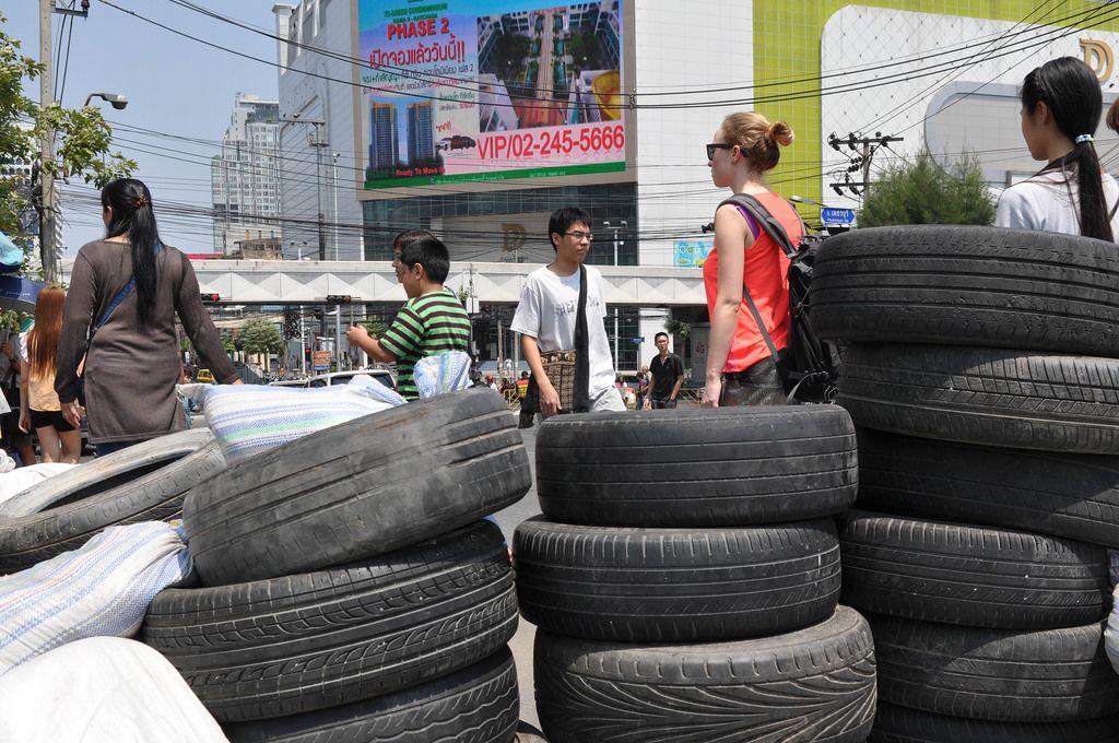 Gebrauchte, abgefahrene Reifen auf der Straße und Passanten im Hintergrund