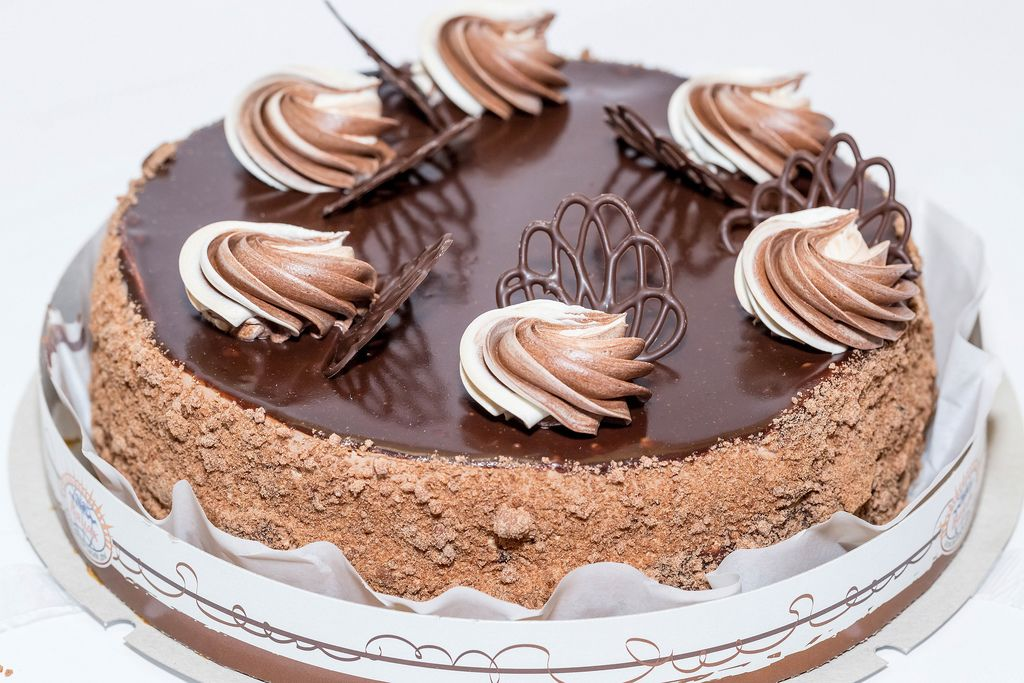 Geburtstagskuchen mit Schokoladenglasur, Nüssen und Sahnedekoration vor weißem Hintergrund