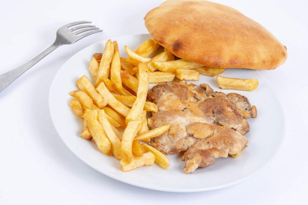 Gegrilltes Hühnerfleisch mit Pommes auf einem weißen Teller
