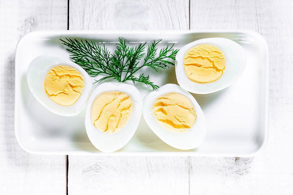 Gekochte Eier, halbiert und mit Dill serviert, auf einem weißen Teller, auf einem Holztisch
