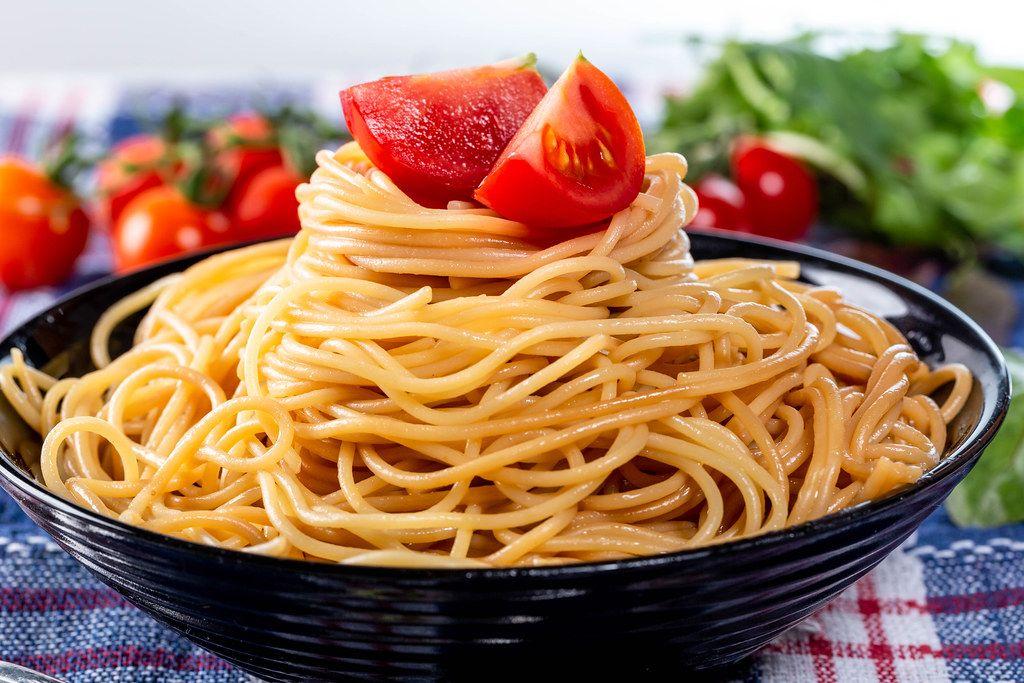 Gekochte Spaghetti in einer Schüssel mit Kräuter und frischem Gemüse