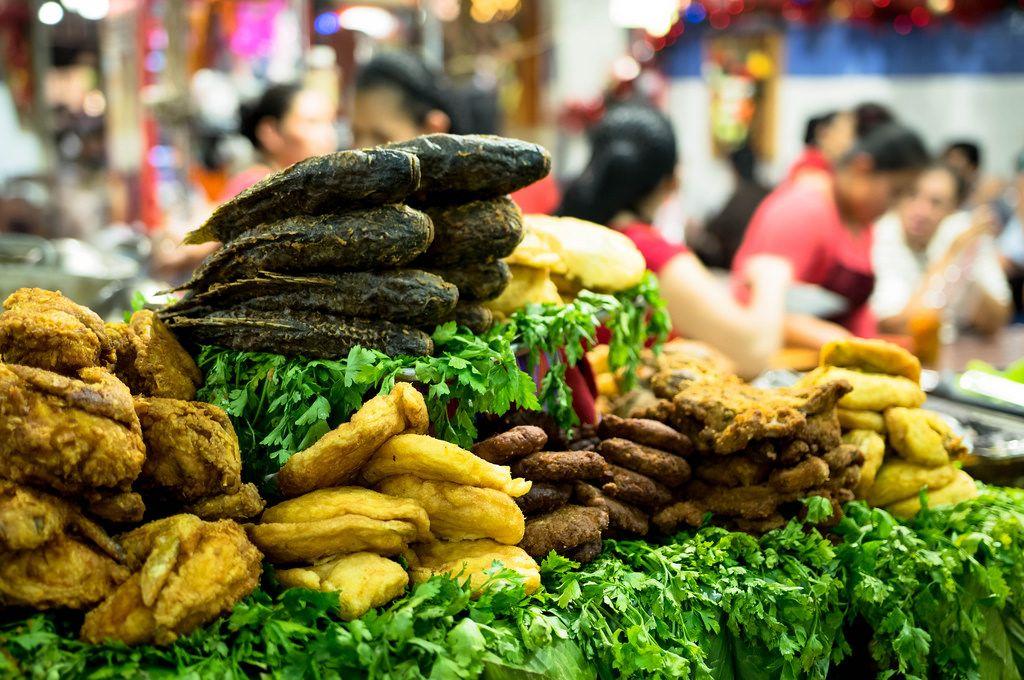 Gekochter Fisch, Hähnchen und Gemüse an einem Stand auf dem Markt