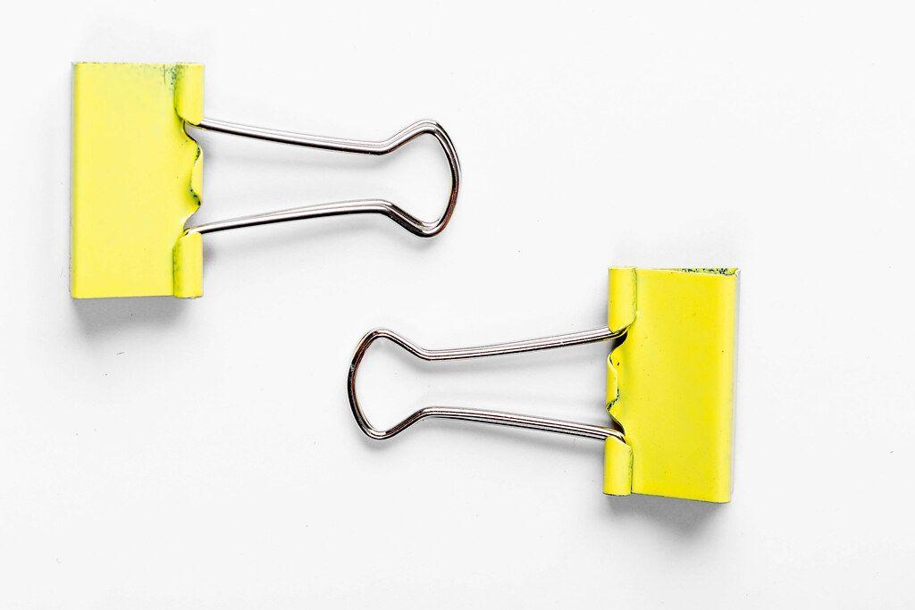 Gelbe Papier-Clips auf weißem Untergrund