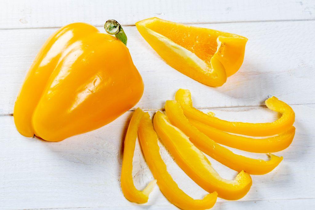 Gelbe Paprika, ganz und in dünne Streifen geschnitten, auf weißem Holztisch