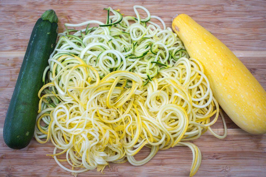 Gelbe und grüne Zucchini auf Holzbrett mit fein geschnittenen Gemüsestreifen aus Zucchini