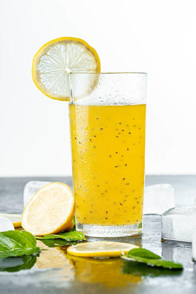 Gelber, sommerlicher Cocktail, mit Minzblättern, Zitrone und Eiswürfeln