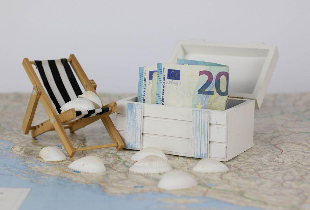 Geld in einer Truhe auf einer Landkarte. Urlaubsgeld