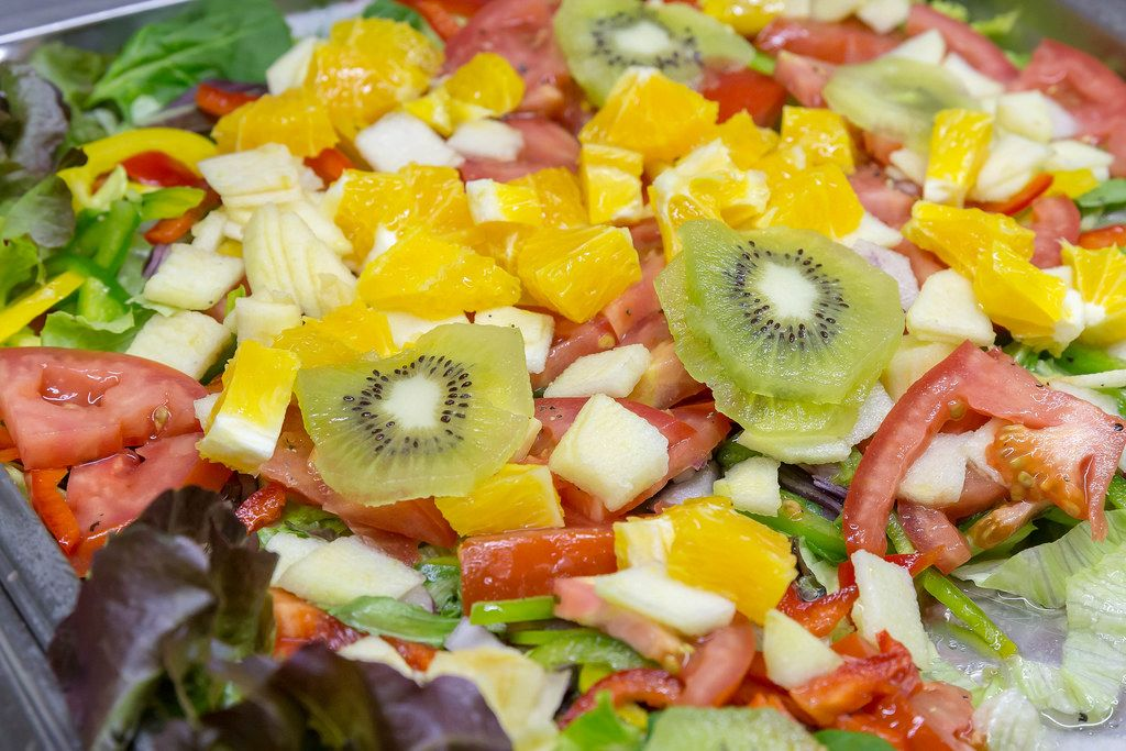 Gemischter Salat mit Früchten und Gemüse - Kiwi, Orangen, Apfel, Tomaten, Paprika
