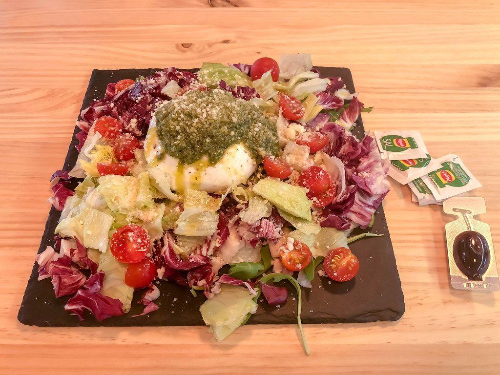 Gemischter Salat mit Kirschtomaten, Mozzarella, Pesto und geriebenem Parmesan Käse auf einer schwarzen Schieferplatte
