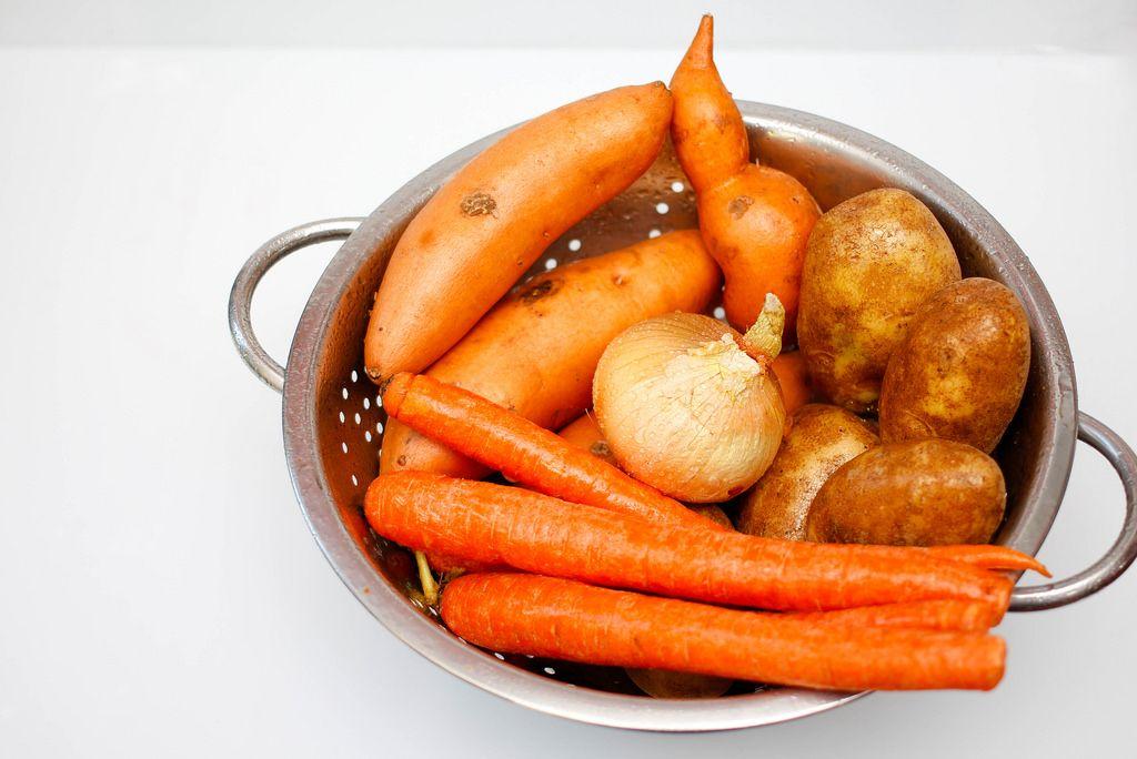 Gemüse im Sieb: Karotten, Süßkartoffeln, Kartoffeln und Zwiebel