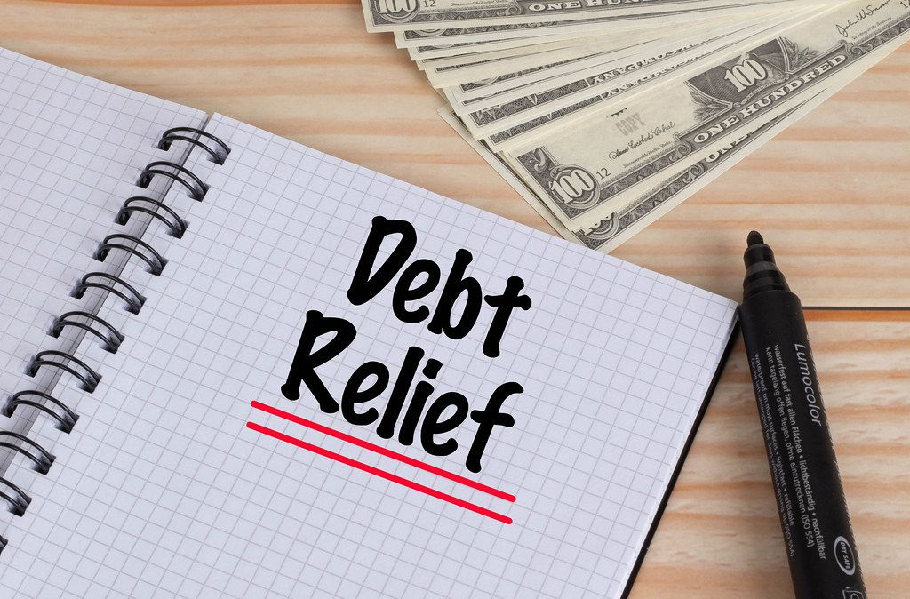 Geöffnetes Notebook mit doppelt rot unterstrichenem schwarzem Text Debt Relief mit schwarzem Filzstift und Dollar Geldscheinen auf einem Holztisch