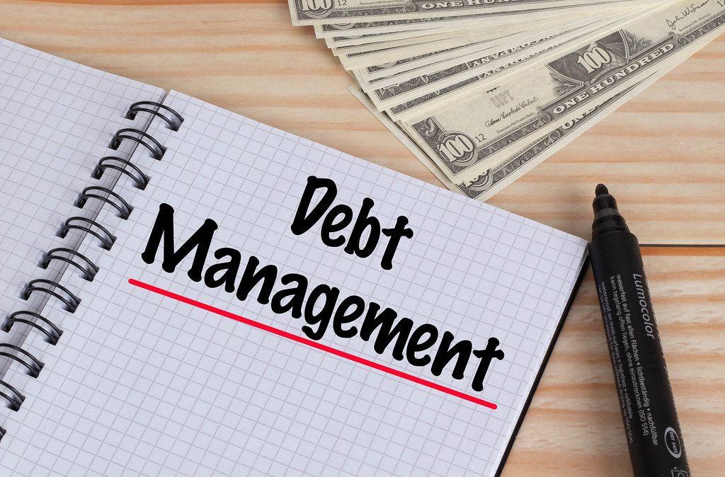 Geöffnetes Notebook mit rot unterstrichenem schwarzem Text Debt Management mit schwarzem Filzstift und Dollar Geldscheinen auf einem Holztisch