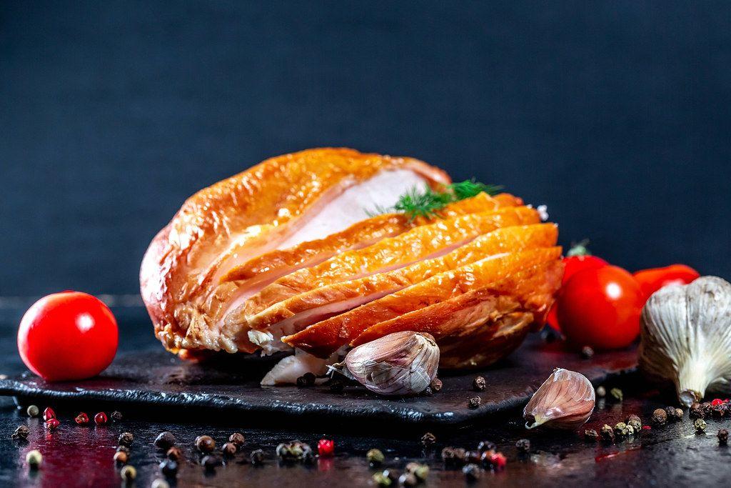 Geräucherte Hühnerbrust mit Tomaten, Knoblauch und Pfefferkörner auf schwarzem Untergrund