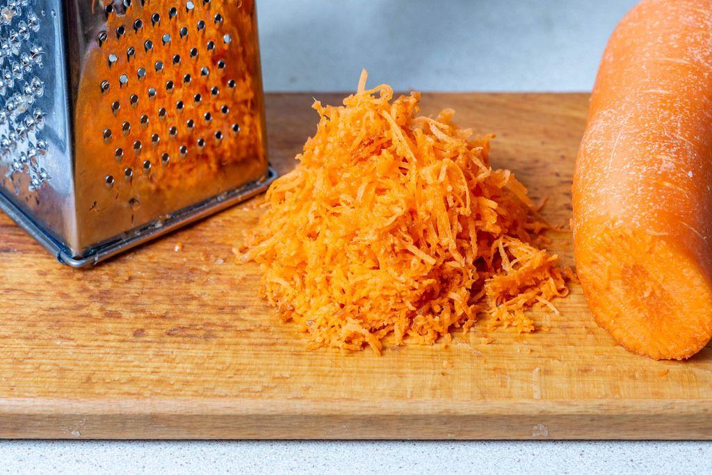 Geriebene Karotten und eine Reibe auf einem Brett