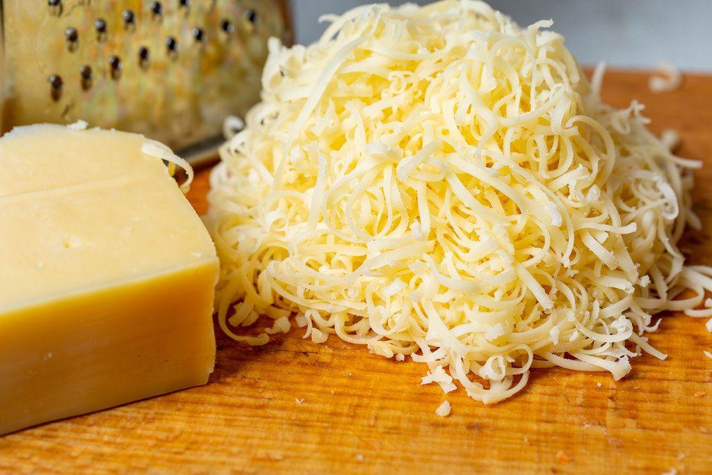 Geriebener Käse mit einem Stück Käse und einer Reibe auf einem Brett