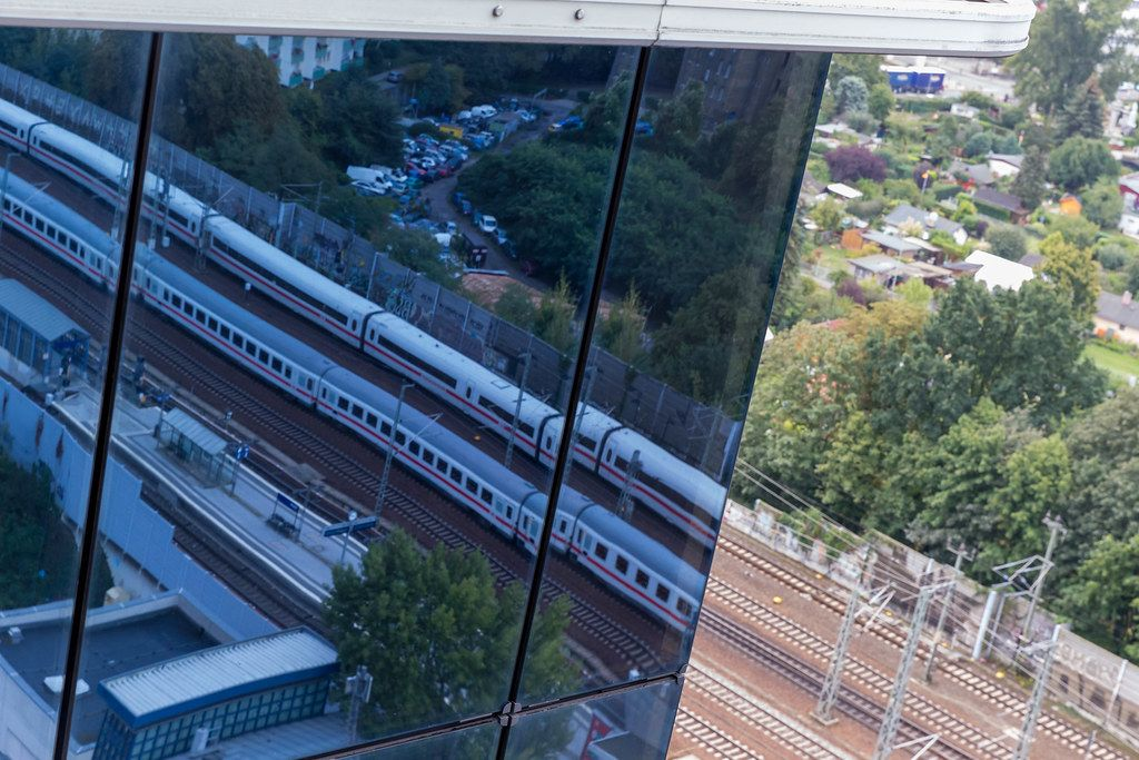German train on the tracks to Spandau train station and reflected image in the glass facade of Spiegel Tower in Berlin