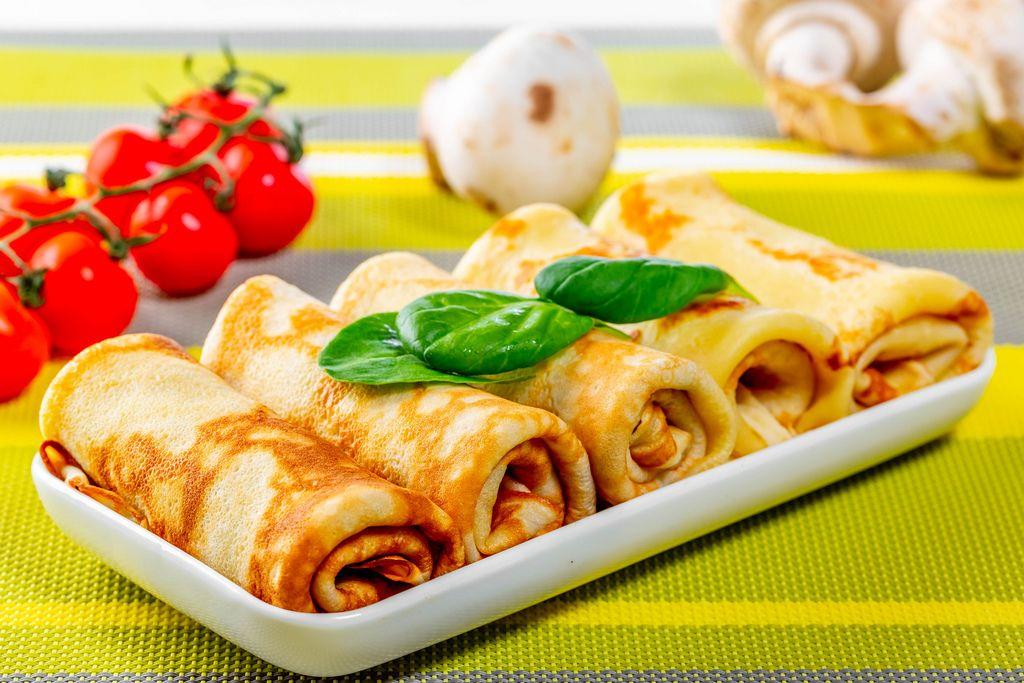 Gerollte Pfannkuchen mit Pilzen, Tomaten und frischem Basilikum auf einem Tisch