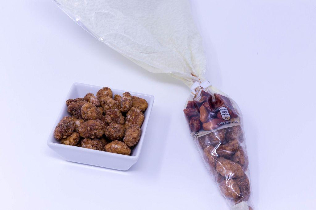 Geröstete Mandeln mit Verpackung auf weißem Hintergrund