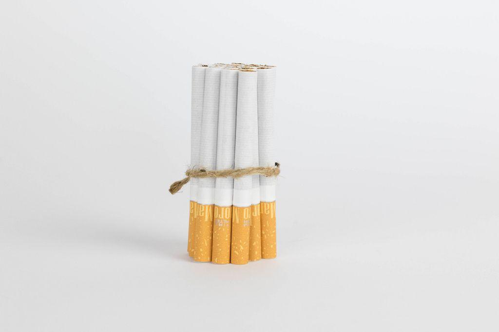 Geschnürte Zigaretten vor weißem Hintergrund