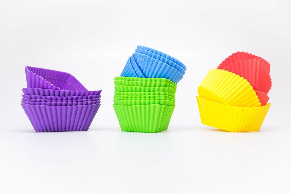 Gestapelte Cupcakeförmchen aus Gummi, in verschiedenen Farben, vor weißem Hintergrund